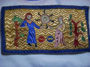 photo of couched embroidery showing two people, one with a coronet, the other with a seneschal symbol next to them, tossing a coin with 7 semi-colons around its edge