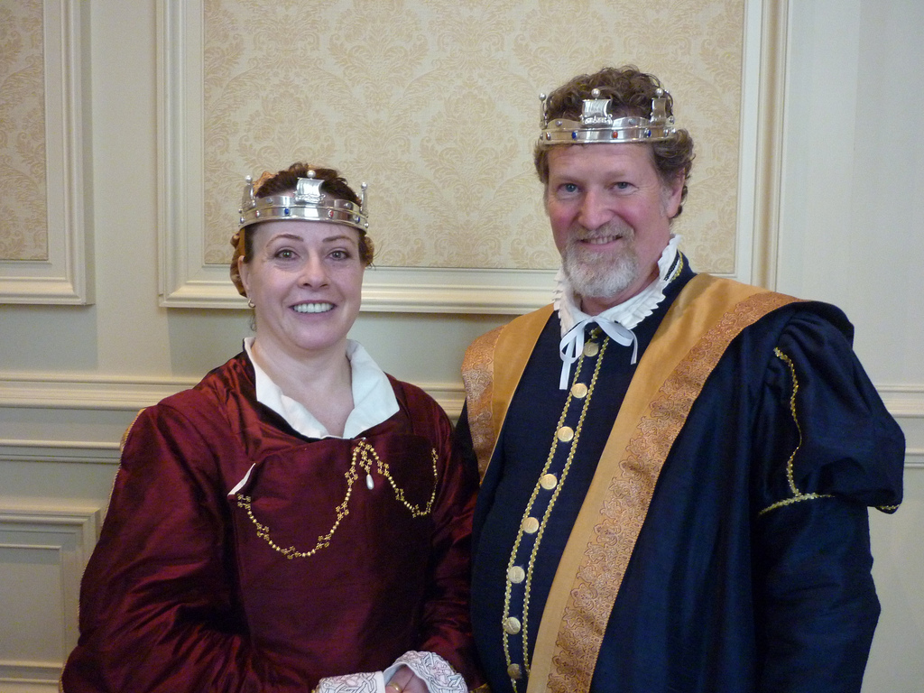 Baroness Sorcha on the left in a red and gold Tudor gown with Baron William on the right in a blue Tudor outfit with gold trim matching the Baroness's